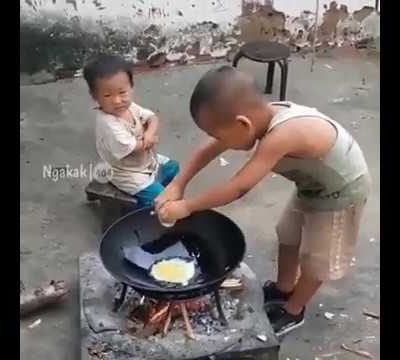 Young boy cooking for his brother